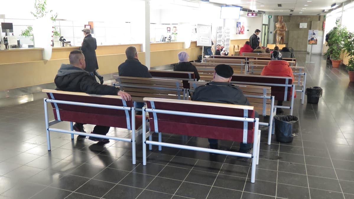 Ihmisiä istuu odottamassa Tampereen poliisiaseman lupapalveluiden aulassa.