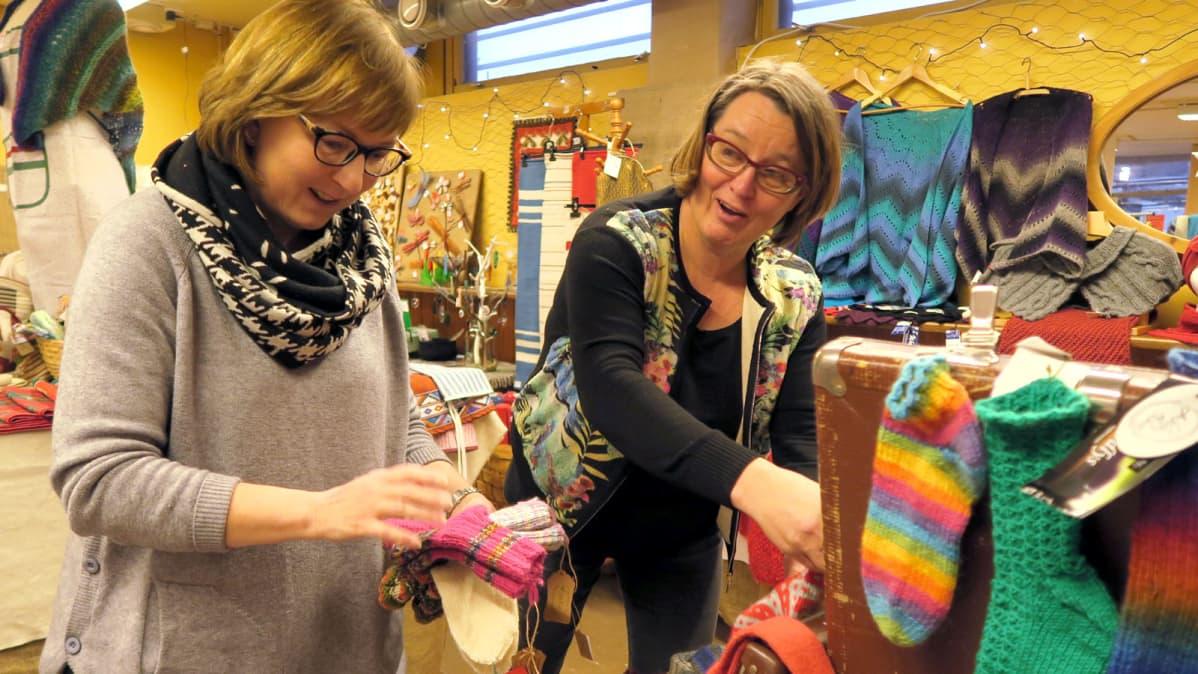 Kaksi naista järjestelee villasukkia joulupuodissa.