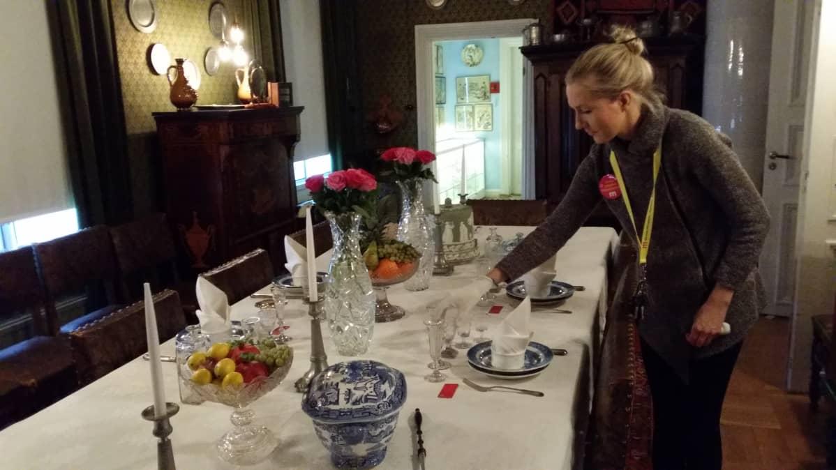 Museoassistentti Anni Mannevaara esittelee joulupöytää.