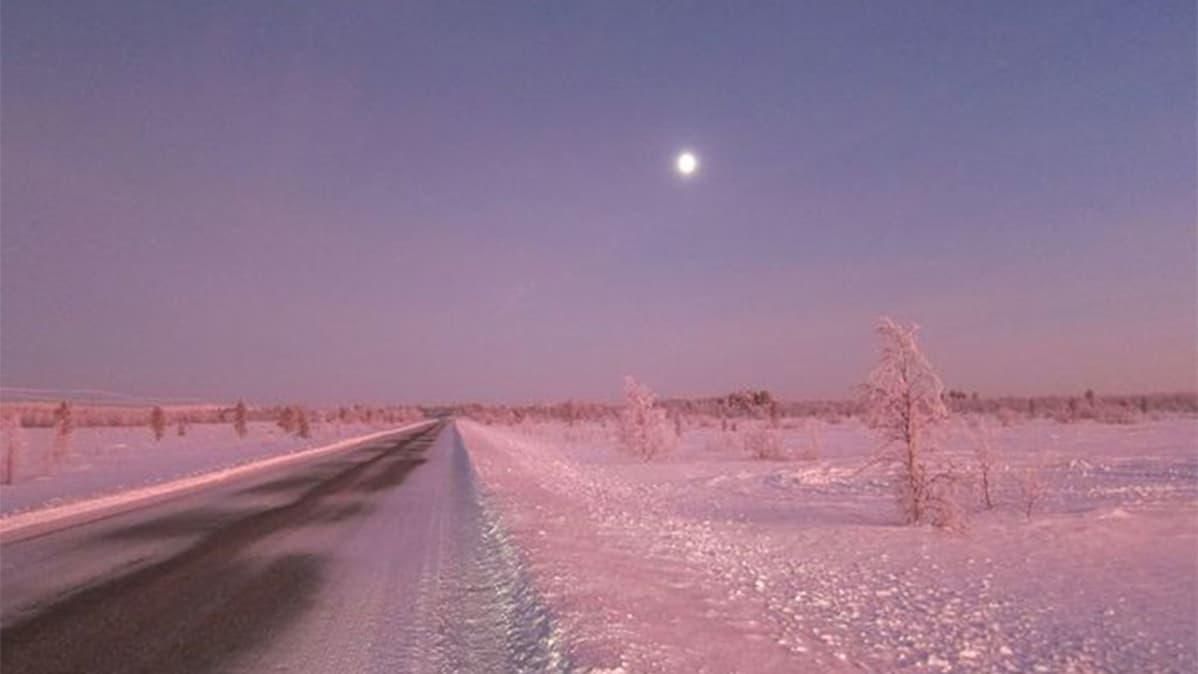 Maantie halkoo lumista, punertavaa maisemaa.
