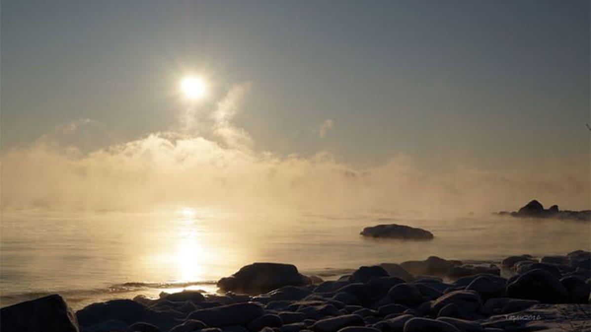 Mereltä, etualalla kivistä rantaa jää päätyy sumuun, aurinko kaiken yllä.