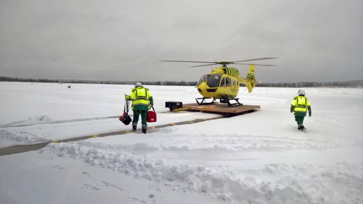 Kaksi miestä kävelemässä FinnHEMSin helikopteriin.