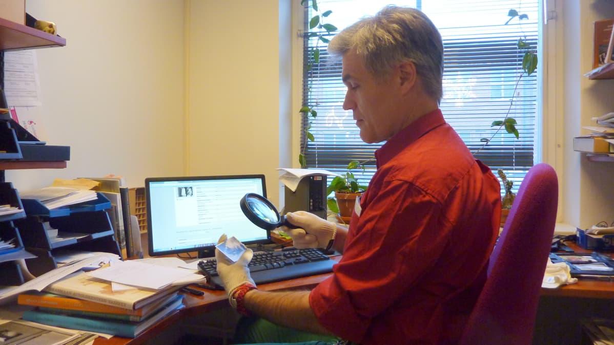 Tutkija Antti Liuttunen tarkastelee toimittajan mukanaan tuomaa vanhaa valokuvaa suurennuslasilla.