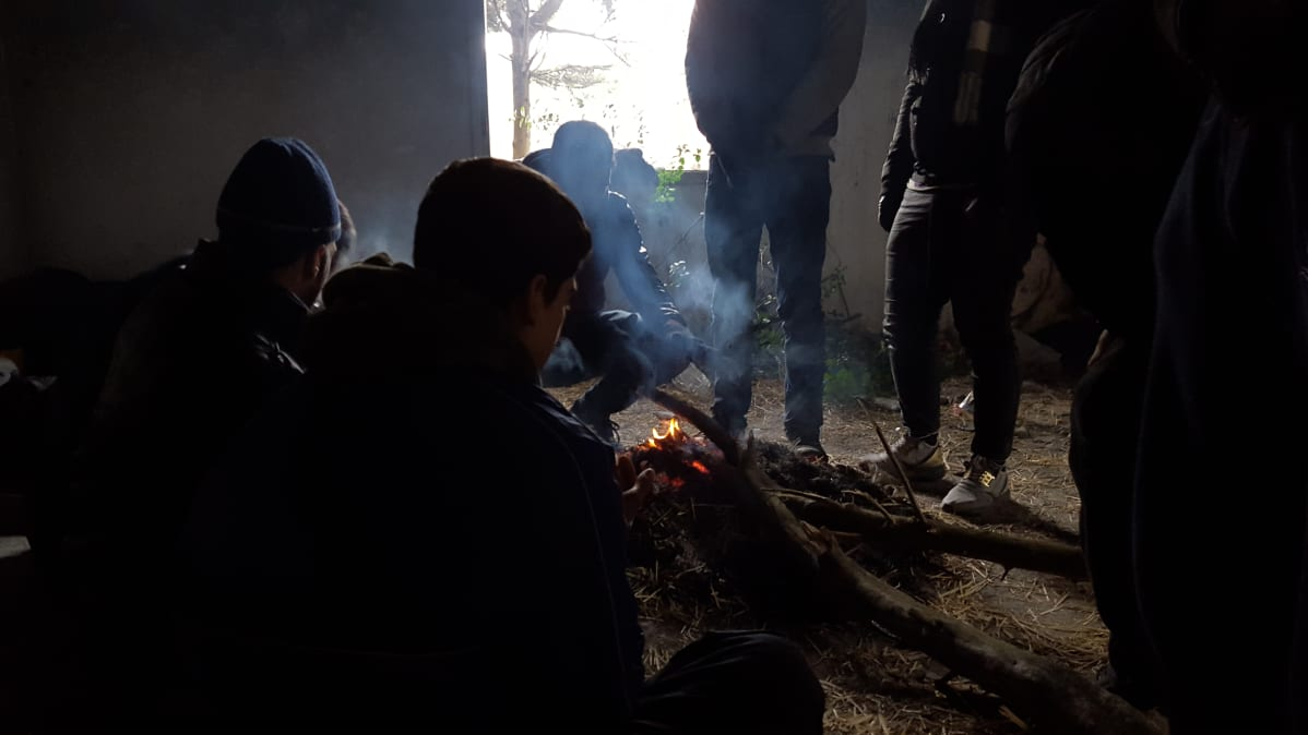 Turvapaikanhakijat lämmittelevät hyläytissä kasarmeissa Pohjois-Kreikassa.