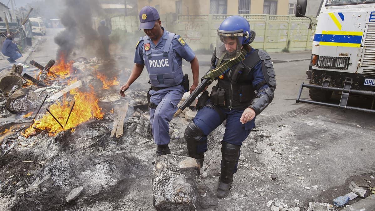 Eteläafrikkalaiset poliisit siivoavat mielenosoituksen jälkiä Cape Townin Masiphurnelelessa syyskuussa 2015.