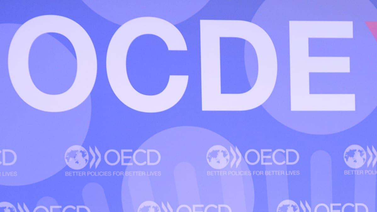 OCDE kirjaimet konferenssitilan seinällä.