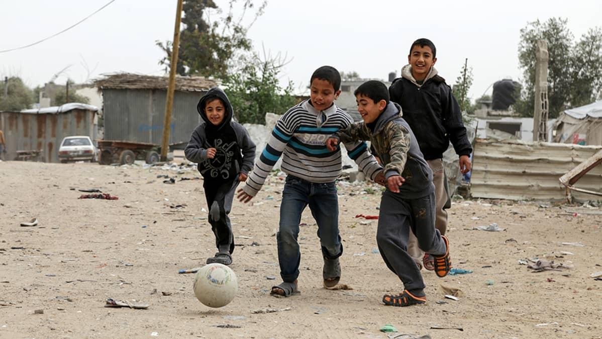 neljä poikaa potkii palloa