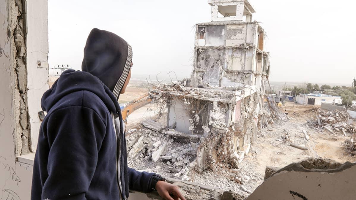 Poika ja taloa purkava kaivinkone