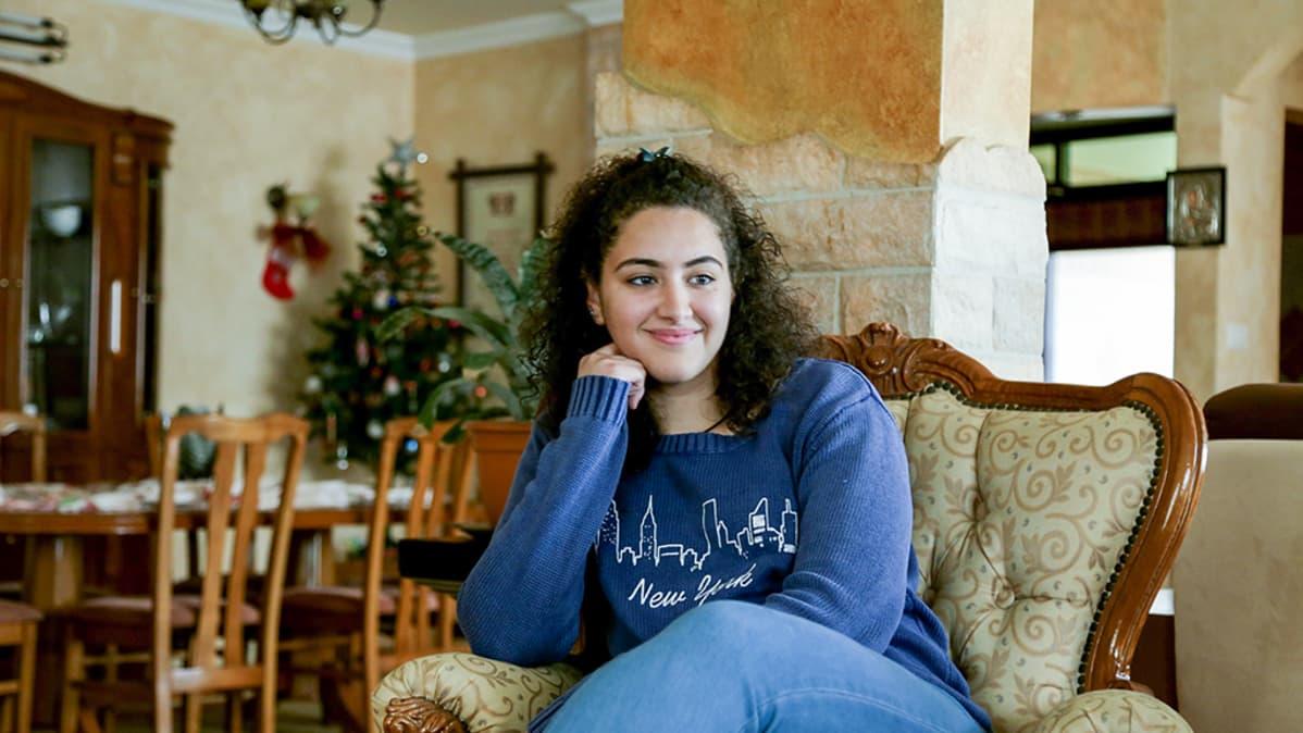 nuori nainen istuu nojatuolissa