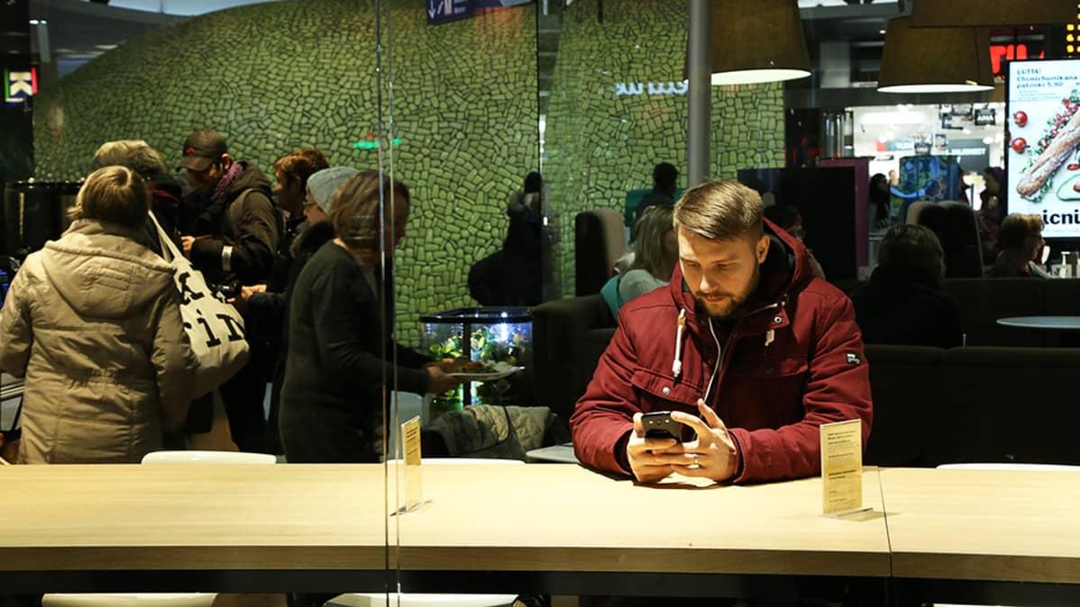 Toimittaja selaa kännykkää.