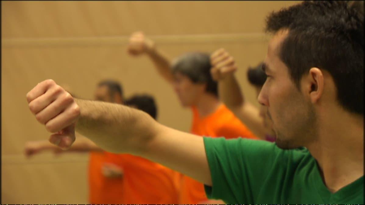 Mies käsi pystyssä karateharjoituksessa.
