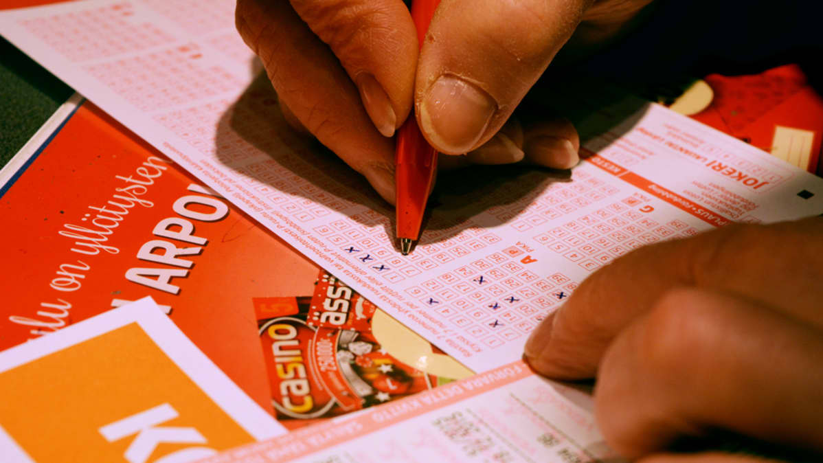 Ihminen täyttää lottokuponkia.