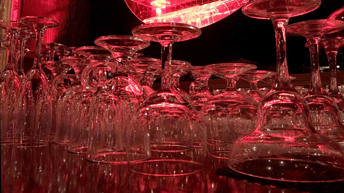 Erilaisia lasisia juomalaseja, kuten konjakki- ja viinilaseja, punaisessa valossa.