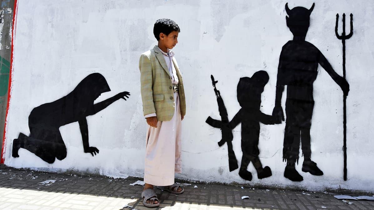 Poika kävelee seinään maalatun graffitin ohi.