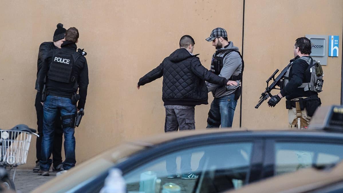 Poliisit tarkastavat jalankulkijoita kadulla.