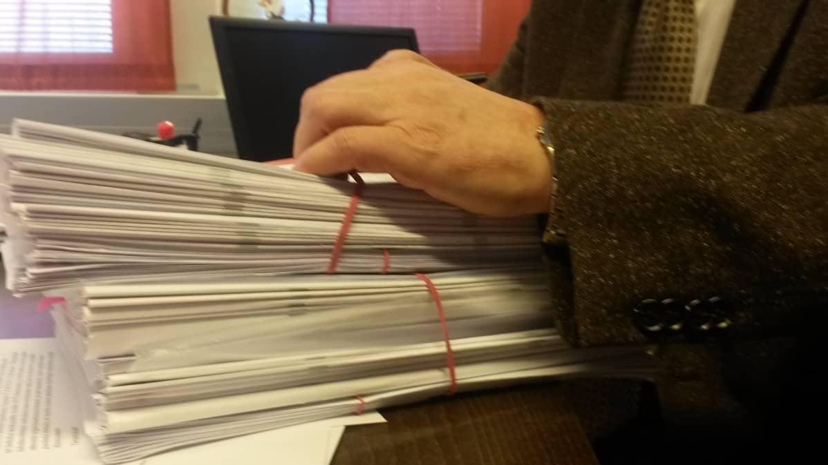 Iso pino papereita syyttäjän pöydällä Oulun syyttäjänvirastossa.