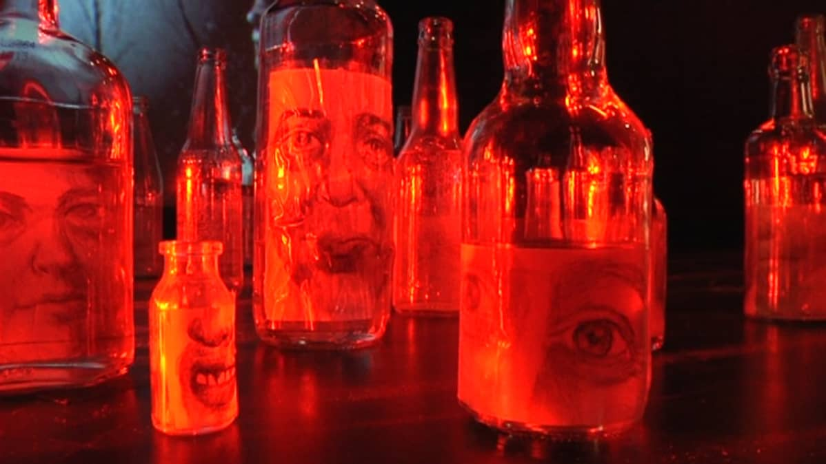 Tyhjät viinapullot ja etikeissä on ihmisen kasvojen kuvia