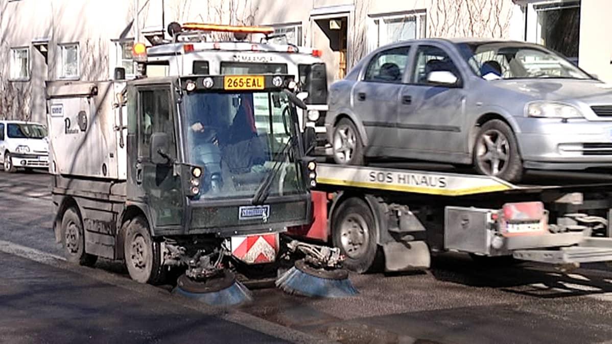 Harjakone siivoaa katua ja hinausauto siirtää henkilöautoa