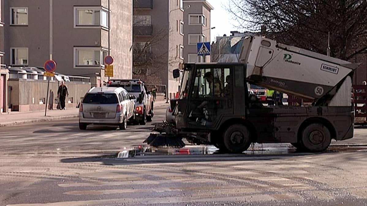 Harjakone siivoaa katua ja hinausauto vie henkilöautoa pois tieltä