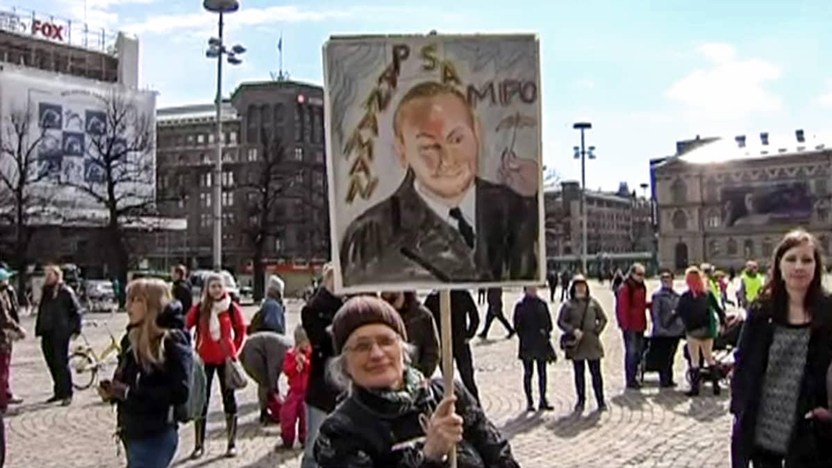 nainen plakaatin  kanssa torilla