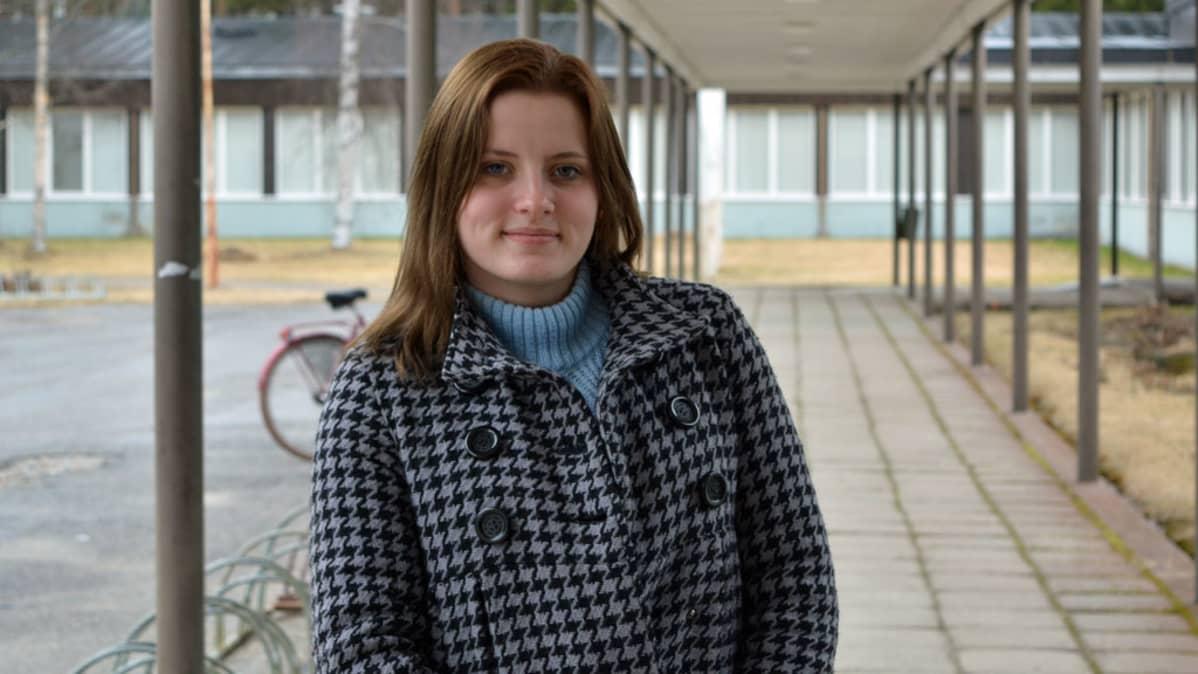 Nuori seisoo koulun pihalla.