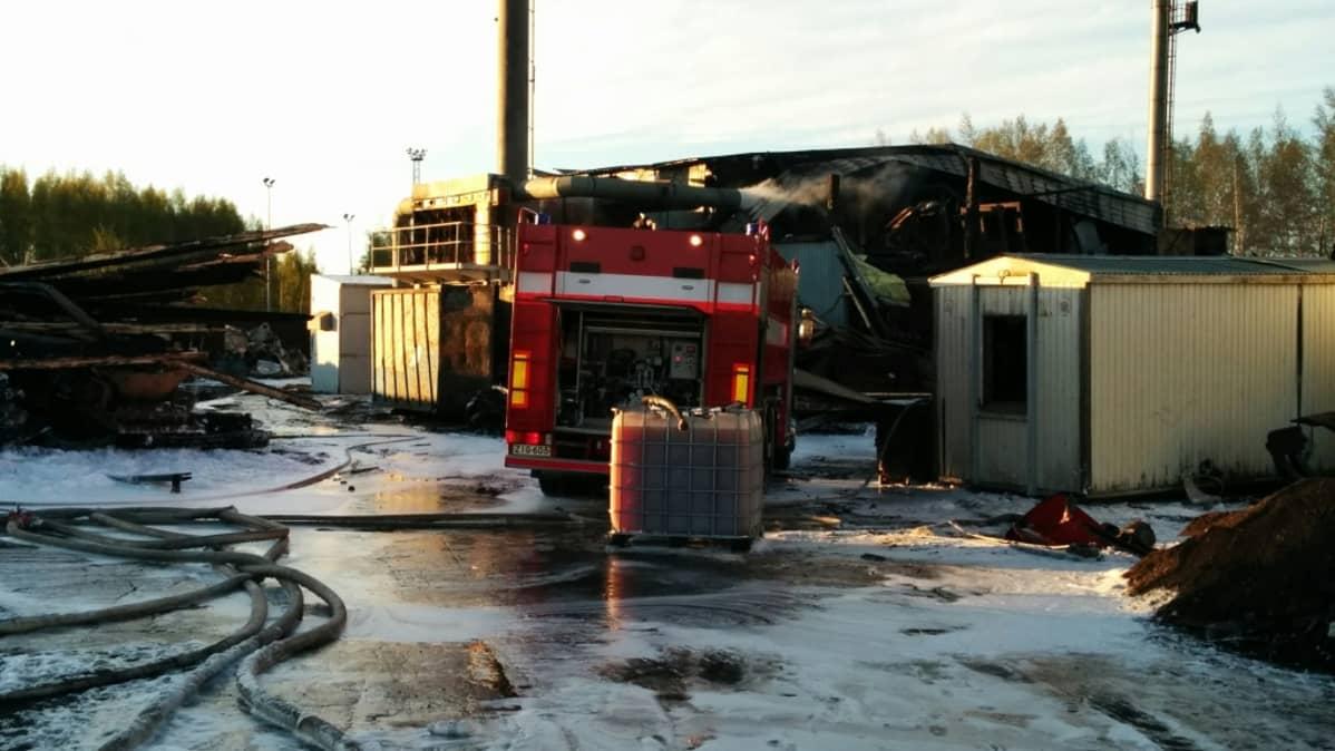 Paloauto palaneen varastorakennuksen edessä