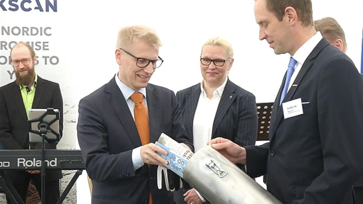 Maatalous- ja ympäristöministeri Kimmo Tiilikainen laittaa lehtiä metallilieriöön