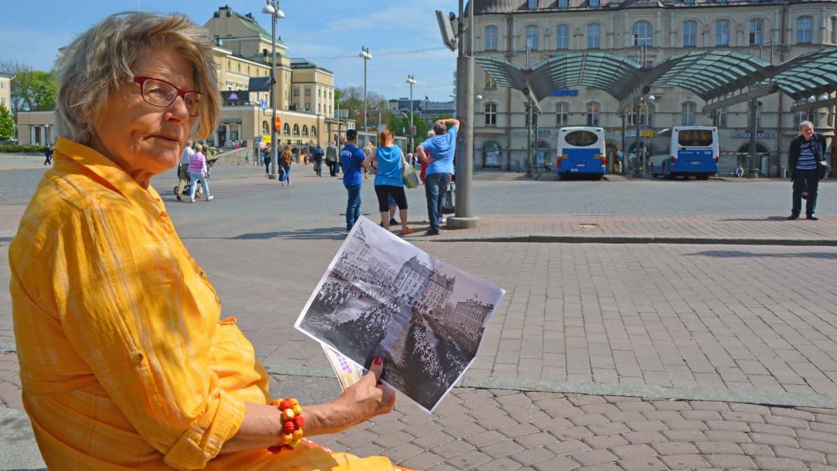 Merja Pikkola istuu Keskustorin penkillä ja katsoo sodanaikaista kuvaa torista.