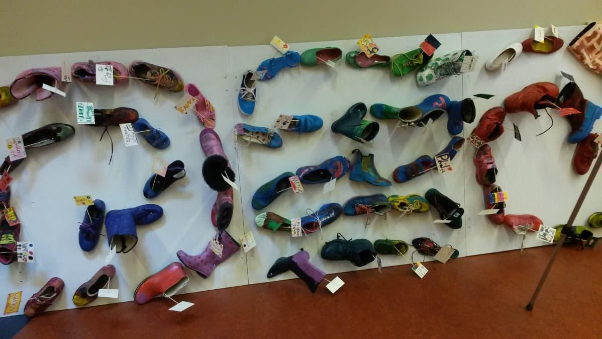 Lasten maalattuja kenkiä aseteltuna taideteokseen.