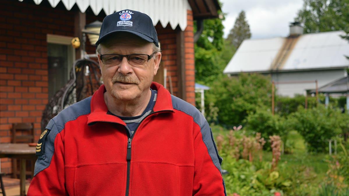 Mies punaisessa fleecessä talon pihassa. Vaatteissa järvipelastajan asemaa osoittavia merkkejä.