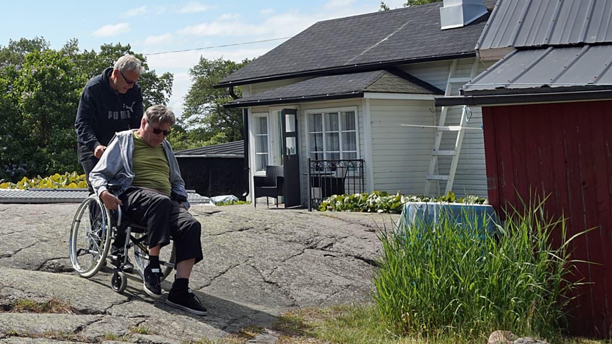 mies auttaa toista pyörätuolissa.