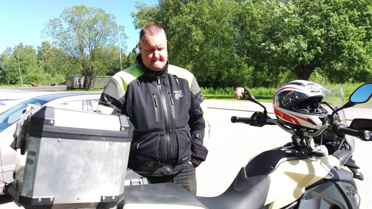 Kuvassa mies seisoo moottoripyörän takana.