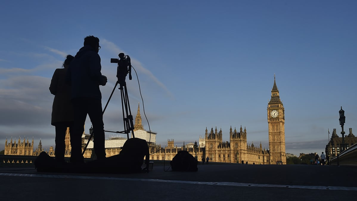 Aurinko nousee Britannian parlamenttitalon ylle.