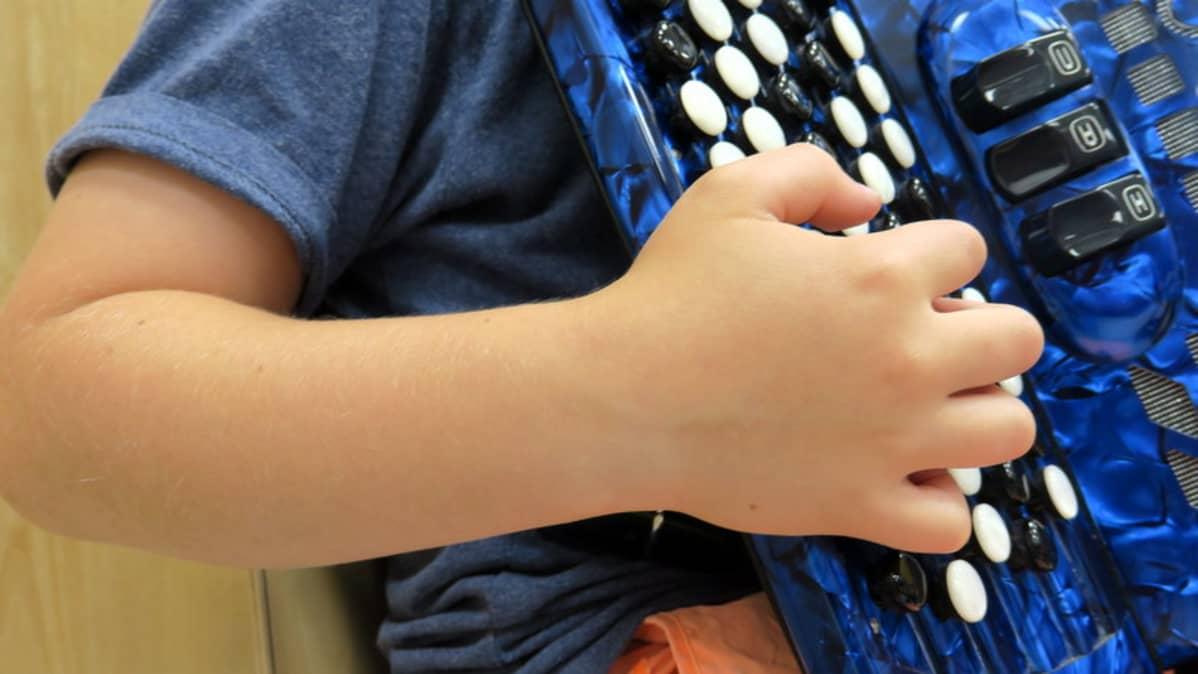Lapsi soittaa harmonikkaa.