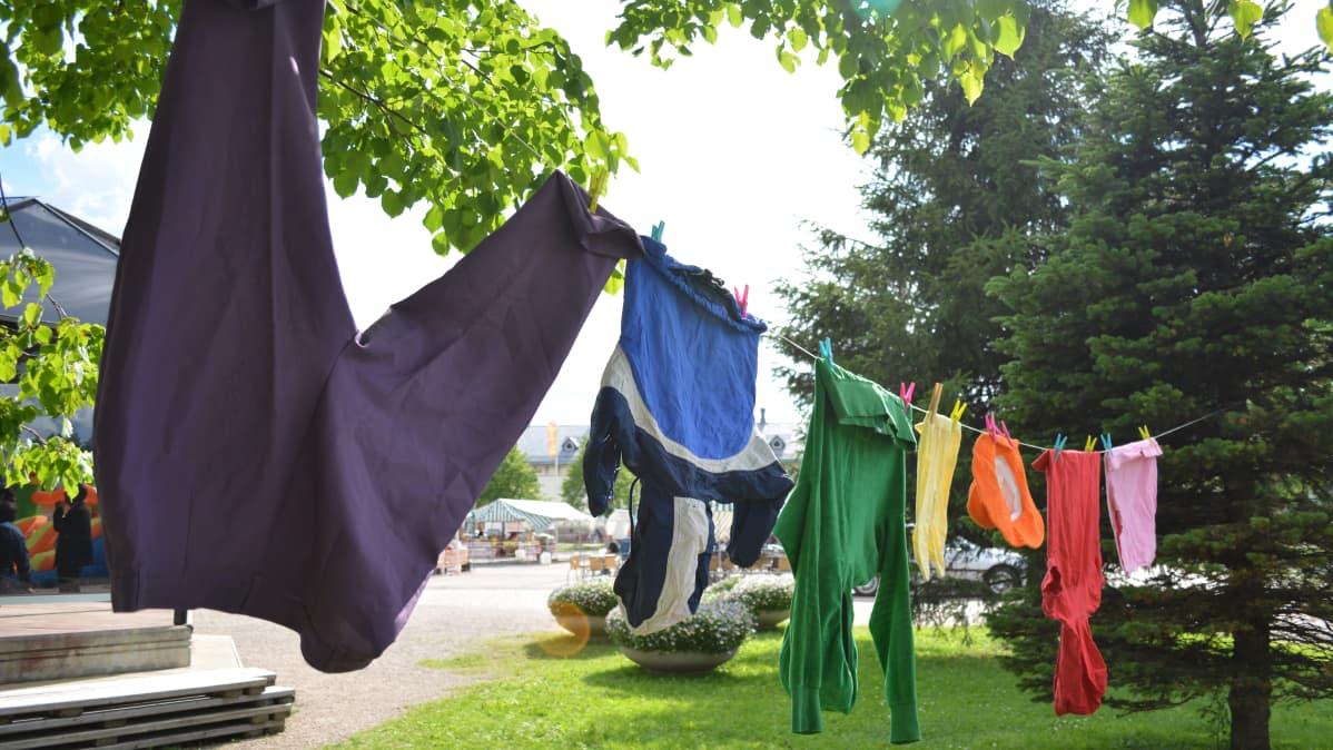 Värikkäitä vaatteita pyykkinarulla.