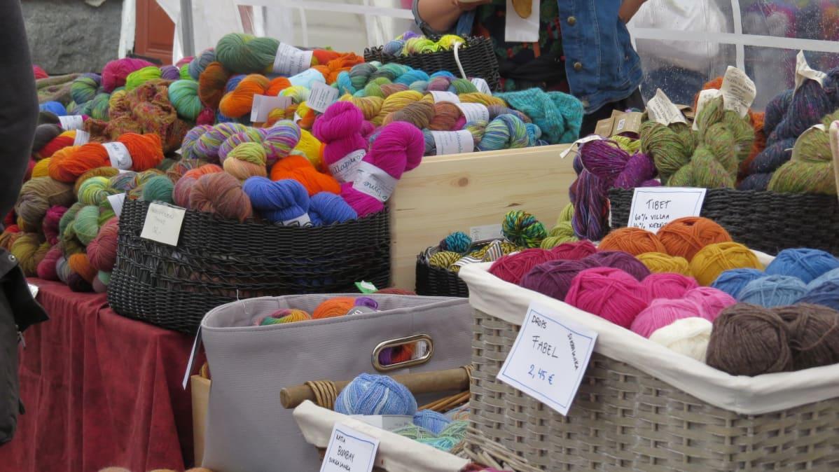 Kirkkaan värisiä lankavyyhtejä markkinapöydällä.