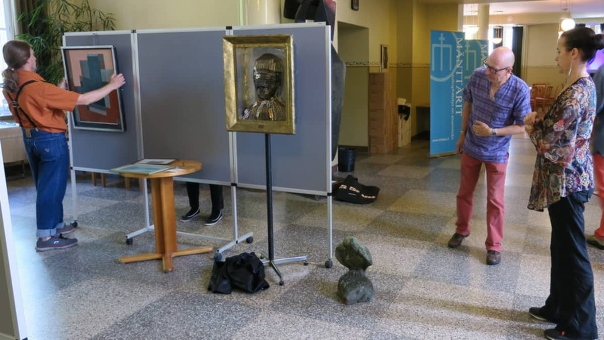 Mies asettaa taulua esille näyttelyssä.