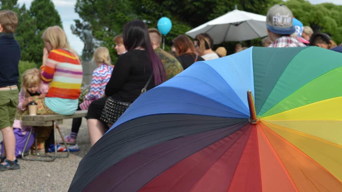 Sateenkaaren värinen sateenvarjo ja ihmisiä.