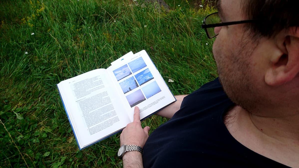mies katselee kirjasta pilven kuvia