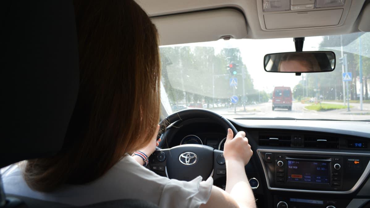 Nainen ajaa autolla.
