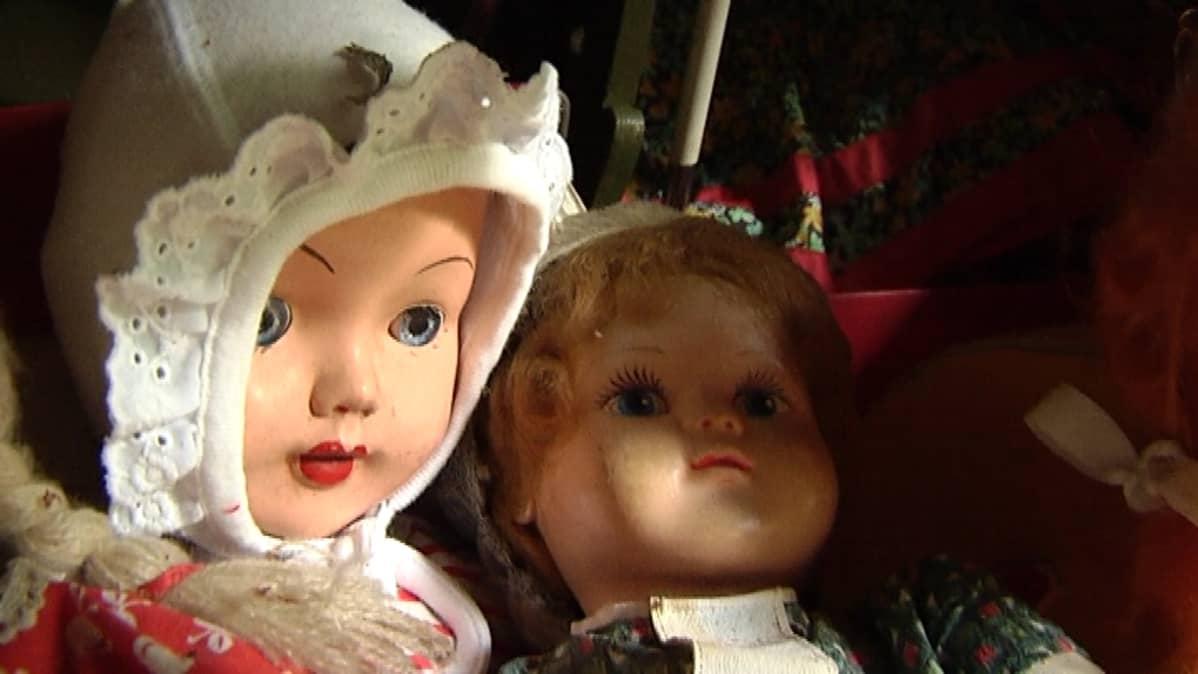 Kaksi vanhaa nukkea istuu vierekkäin.