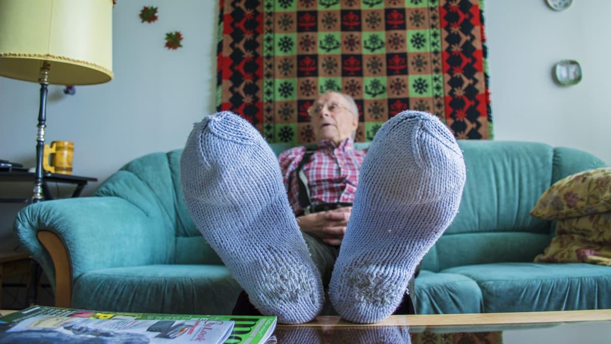 Matti Hakola oikaisee jalkansa sohvapöydälle.