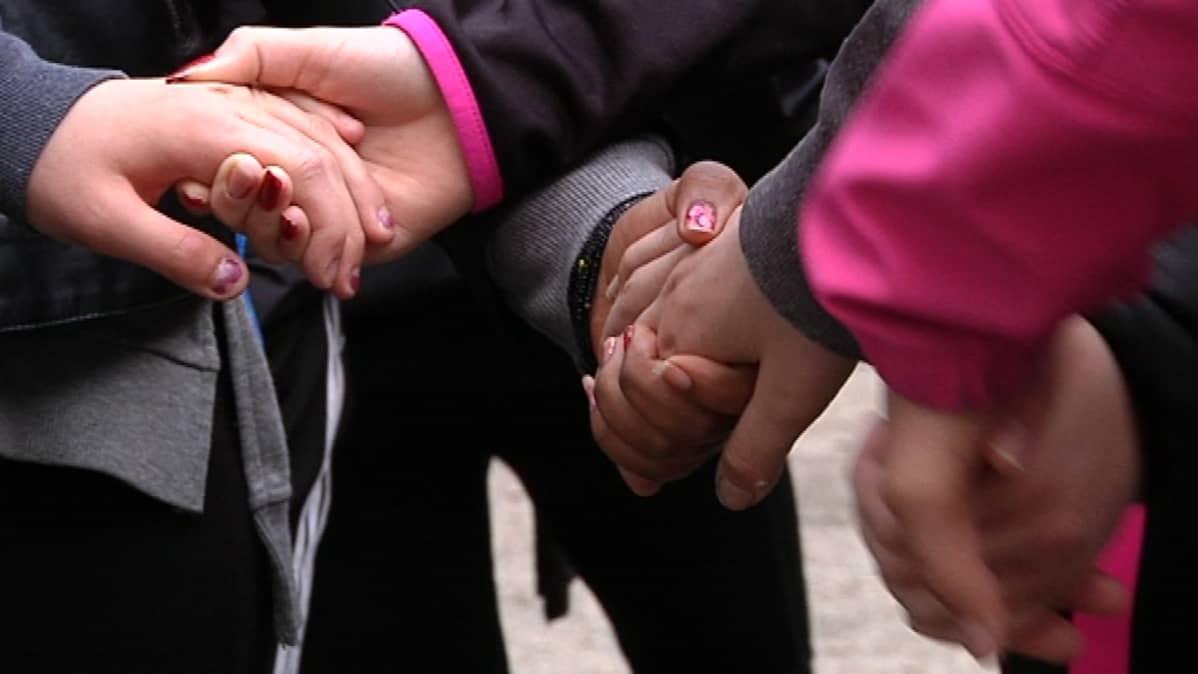 Oppilaat pitävät toisiaan käsistä kiinni ryhmäytymispäivänä.