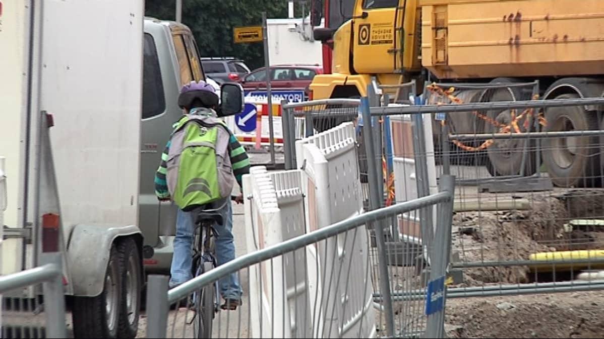 Poika pyöräilee työmaan vieressä liikenteen keskellä.