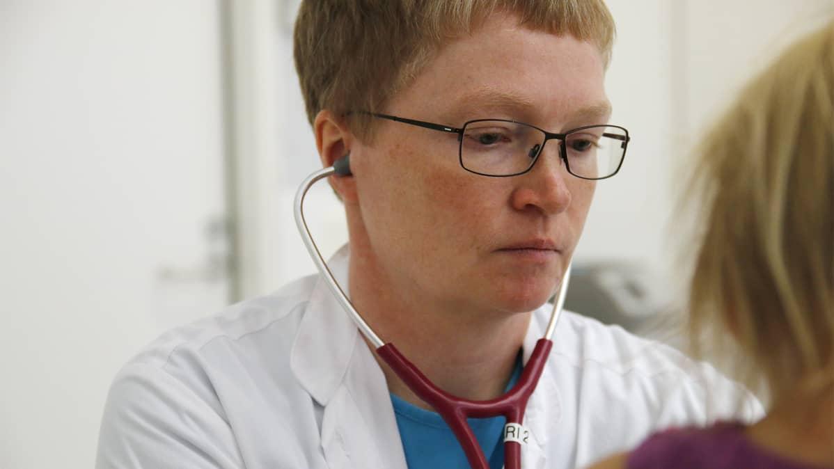 Lääkäri kuuntelee stetoskoopilla henkilöä.