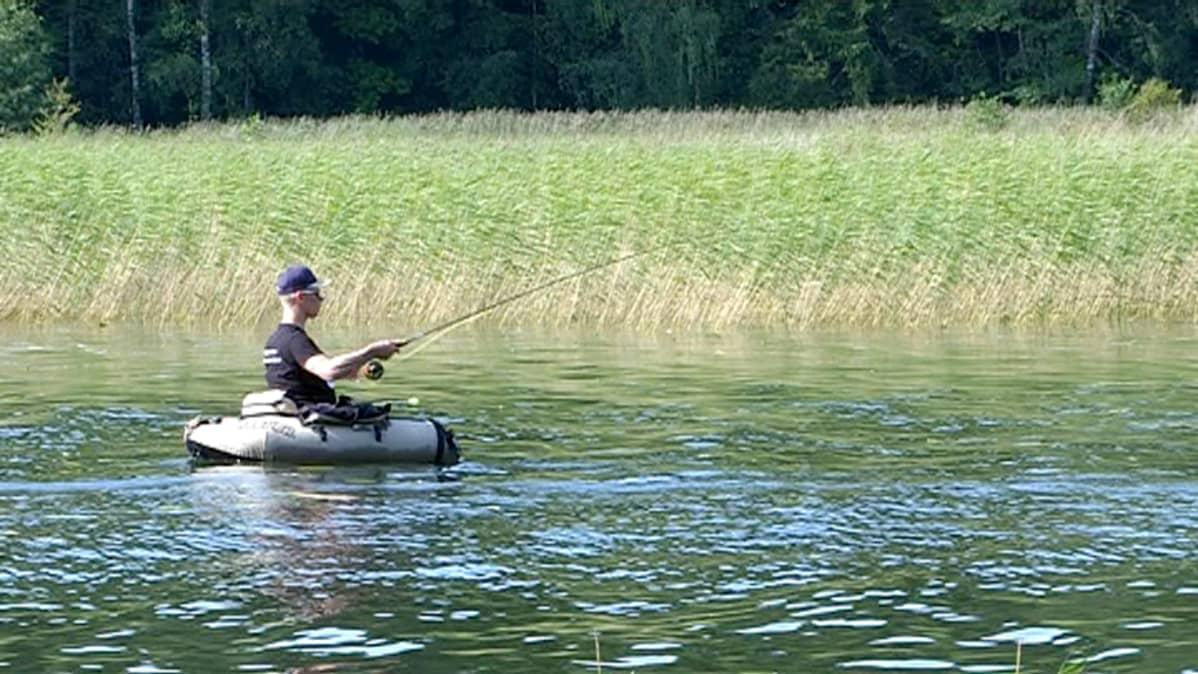 Mies kalastaa perho-ongella kelluntarenkaassa.