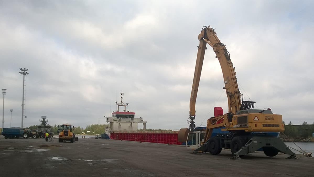 Rahtialus Rahjan laiturissa, etualalla nosturi, taustalla satama-alueella lastauskalustoa.