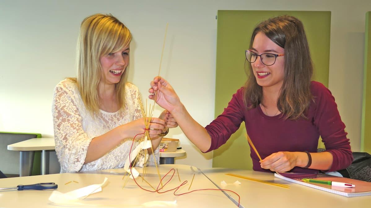 Jenna Rosenberg (vasemmalla) tekemässä yhdessä opiskelijatoverinsa kanssa spagetti-vaahtokarkki-rakennelmaa.