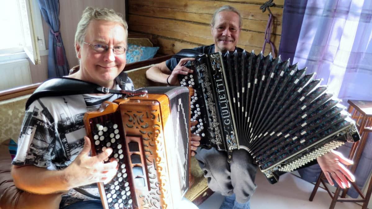 Kaksi miestä soittavat harmonikkaa.