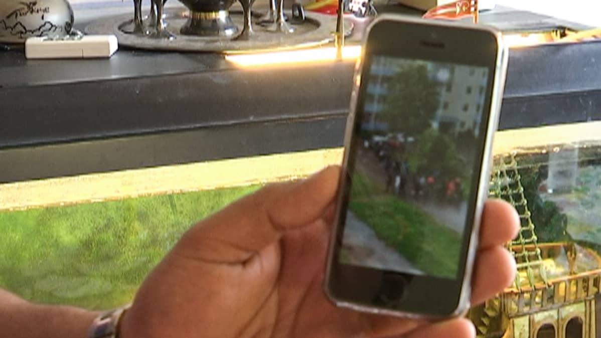 Henkilö näyttää videokuvaa kännykän näytöltä.